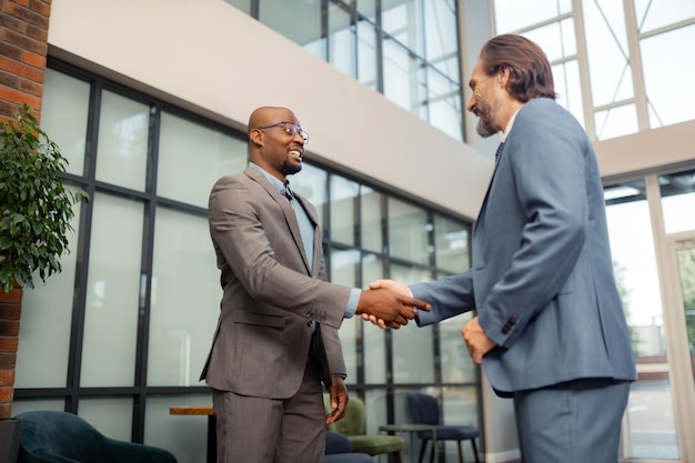 Человек, пожимая руку. темнокожий бизнесмен в очках пожимает руку своему инвестору