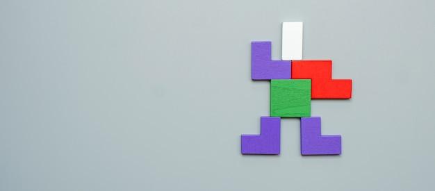 회색에 다채로운 나무 퍼즐 조각의 남자 모양 블록. 논리적 사고, 비즈니스 로직, 수수께끼, 결정, 솔루션, 합리적 및 아이디어 개념