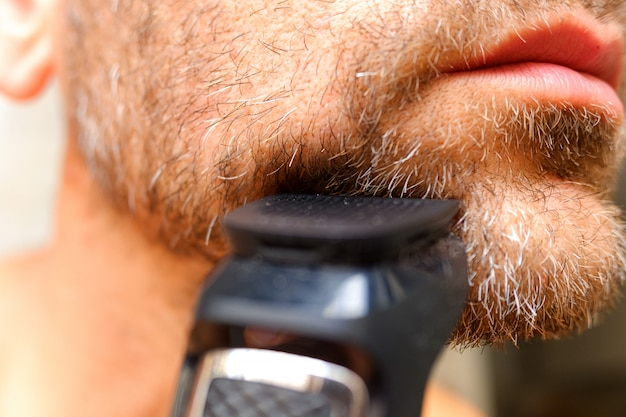A man shaves his beard using an electric razor.