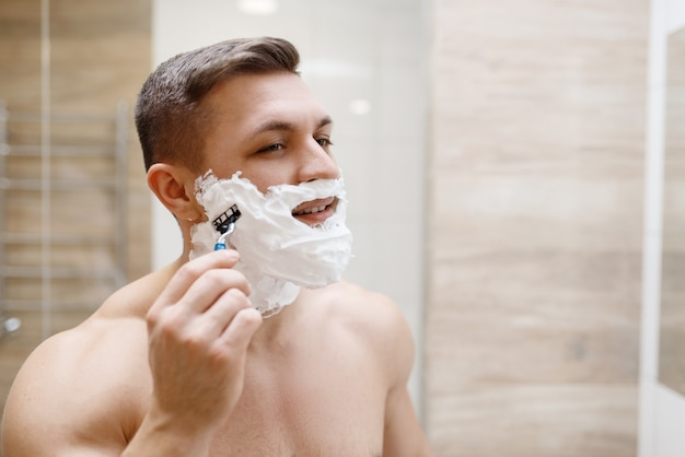 Man shaves his beard with razor in bathroom, routine morning hygiene.