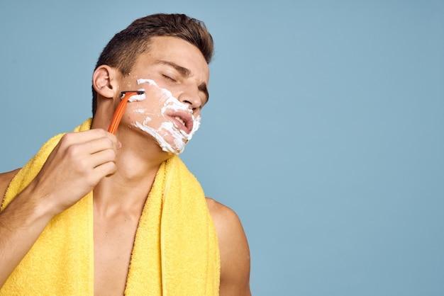 Мужчина бреет лицо бритвой и пеной для бритья
