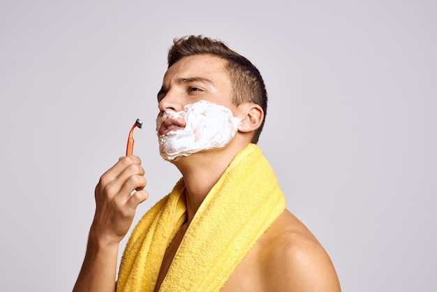 シェービングフォームとかみそりで顔を剃る男