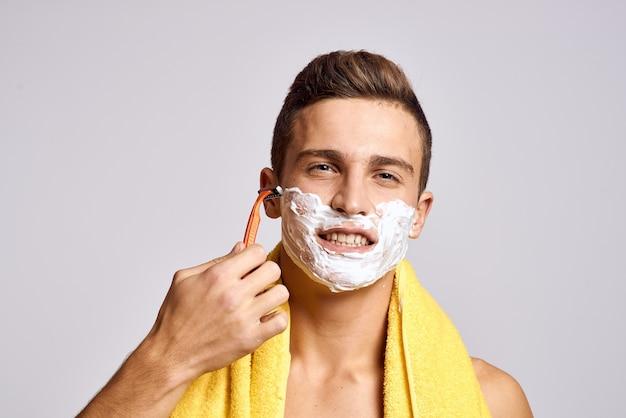 男はシェービングフォームでかみそりで顔を剃る