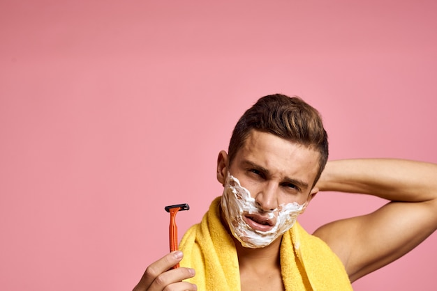 Man shaves his face with a razor with shaving foam
