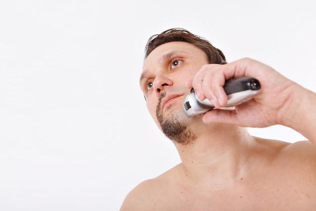 男は無精ひげを剃る。男は電気かみそりでひげを掃除します。バスルームでの朝のトリートメント。ひげの半分のクローズアップ。コピースペース