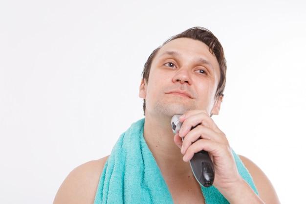 男は無精ひげを剃る。男はひげを電気かみそりで掃除します。バスルームでの朝のトリートメント。