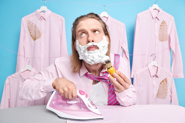 Man shaves and irons clothes at same time uses electric iron poses in laundry room gets dressed for special occasion. domestic work concept