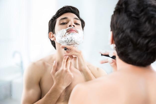 Man shaving in the bathroom.
