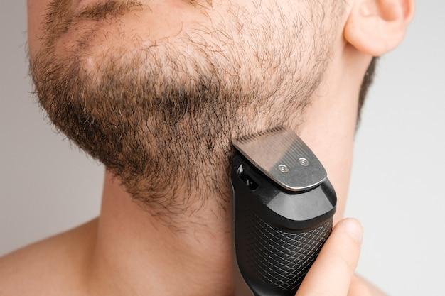 電気かみそりでひげと首を剃る男。毎朝の日課。トリマーでひげをトリミングします。