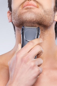 Man shaving. close up of young man shaving his face with electric shaver while standing against grey background