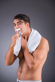 Man shaving on dark background