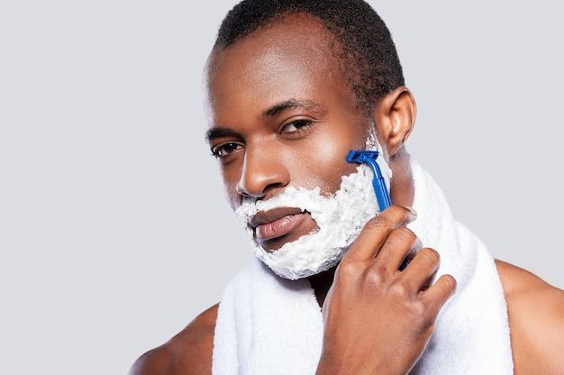 Мужчина бреется. африканский красавец без рубашки бреет лицо и смотрит в камеру, стоя на сером фоне