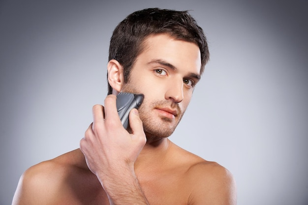 Man shaving. handsome young man shaving his face with electric shaver and looking at camera while standing isolated on grey background