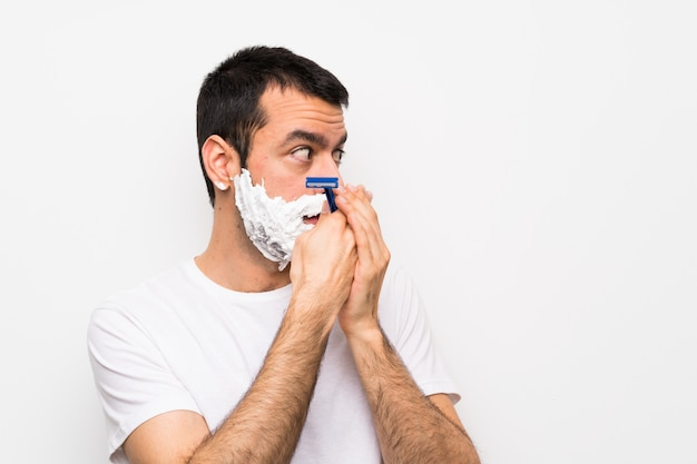 Man shaving his beard covering mouth and looking to the side