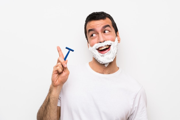 Man shaving his beard over isolated white background intending to realizes the solution while lifting a finger up