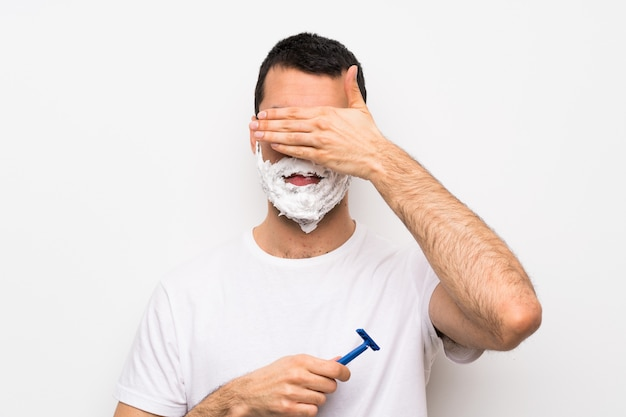 Man shaving his beard over isolated white covering eyes by hands. do not want to see something