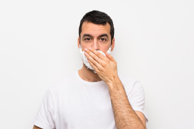 Man shaving his beard over isolated white  covering mouth with hands
