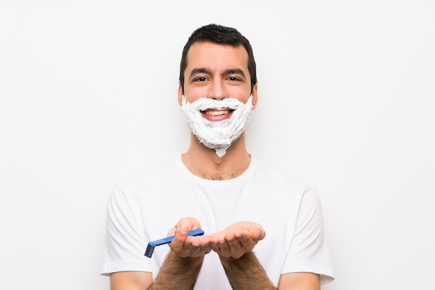 Man shaving his beard over isolated white wall holding copyspace imaginary on the palm to insert an ad
