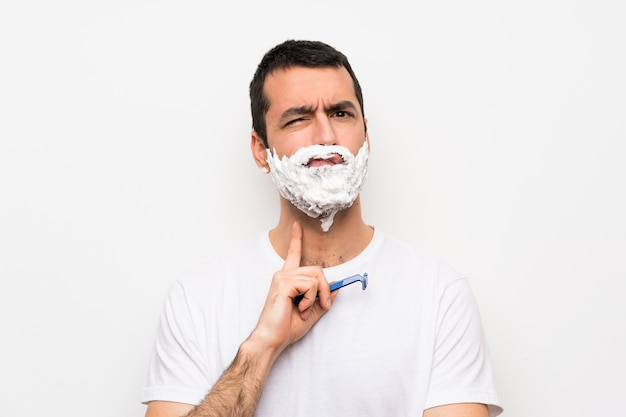 Man shaving his beard over isolated white wall looking front