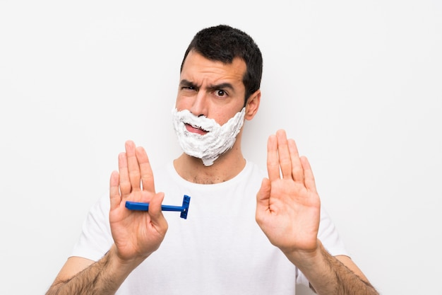 Man shaving his beard over isolated white wall making stop gesture and disappointed