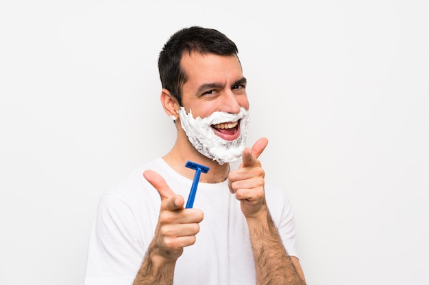 Man shaving his beard over isolated white wall pointing to the front and smiling