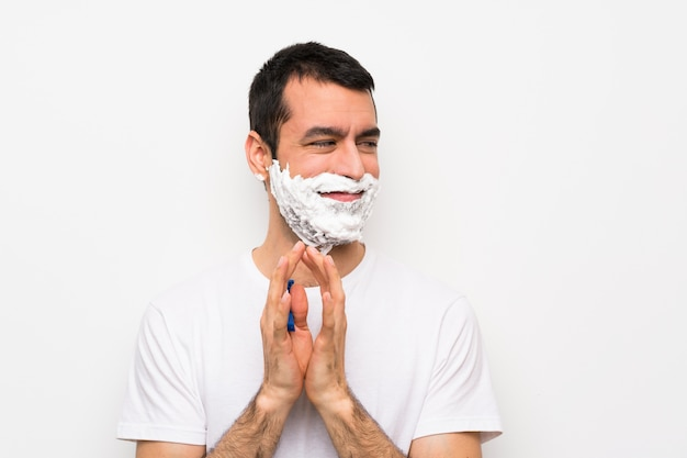 Man shaving his beard over isolated white wall scheming something