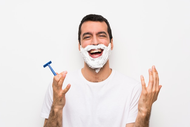 Man shaving his beard over isolated white wall smiling a lot