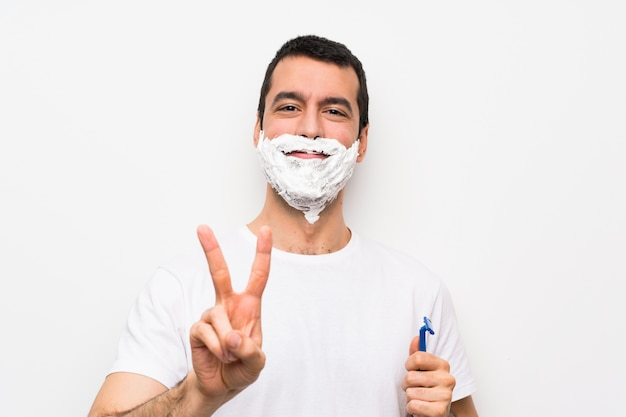 Man shaving his beard white smiling and showing victory sign
