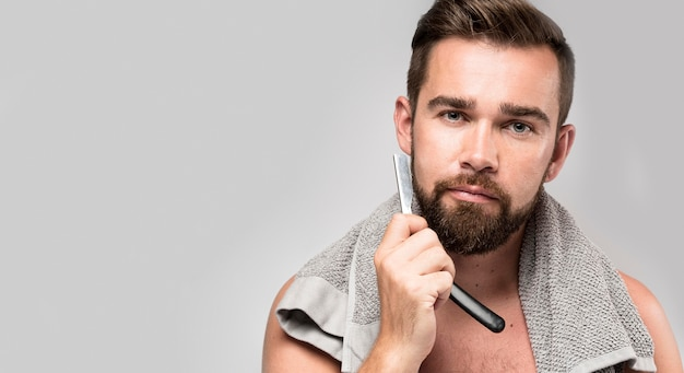Man shaving his beard with copy space