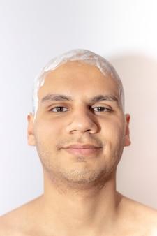 하얀 거품을 사용 하여 그의 머리를 면도하는 남자