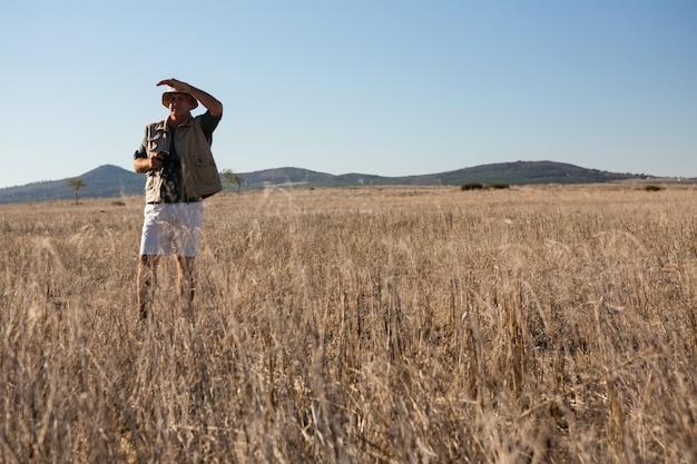 Man shielding eyes on landscape