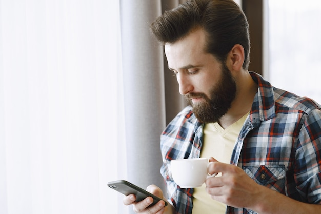 Man in a shirt and a cell. guy with coffee and phone. man by the window.
