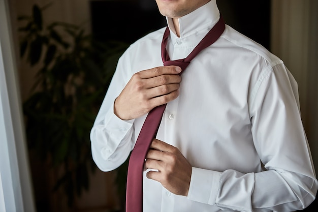 Man in shirt dressing up and adjusting tie on neck at home