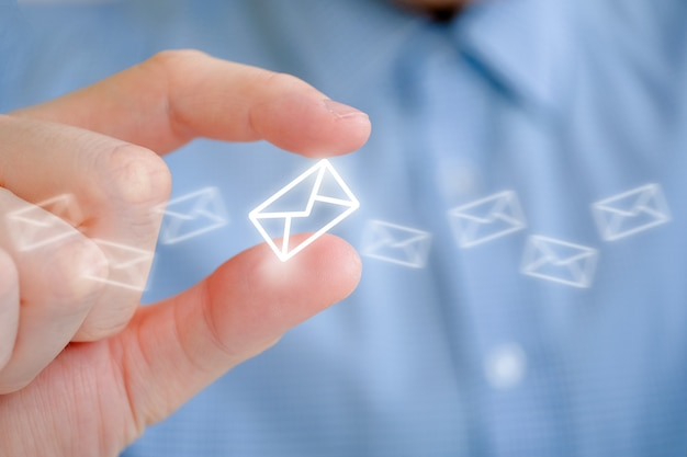 A man in a shirt holds an abstract envelope icon with his hand. the concept of mail and its sending.