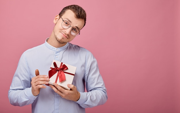 Man in shirt holds gift in box, looking straight