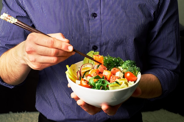Man in a shirt holds poke bowl with salmon, broccoli, rice, carrots cheese and chuha