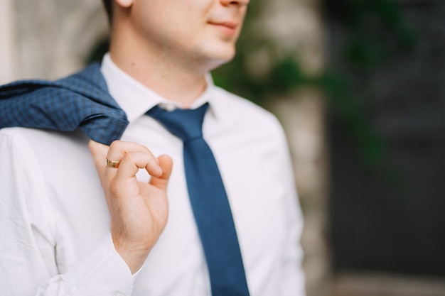 A man in a shirt and tie holds a jacket on his shoulder, close-up