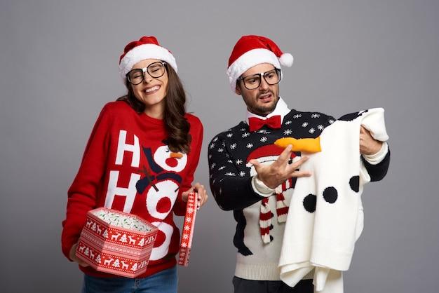 面白いクリスマスセーターを贈られてショックを受けた男