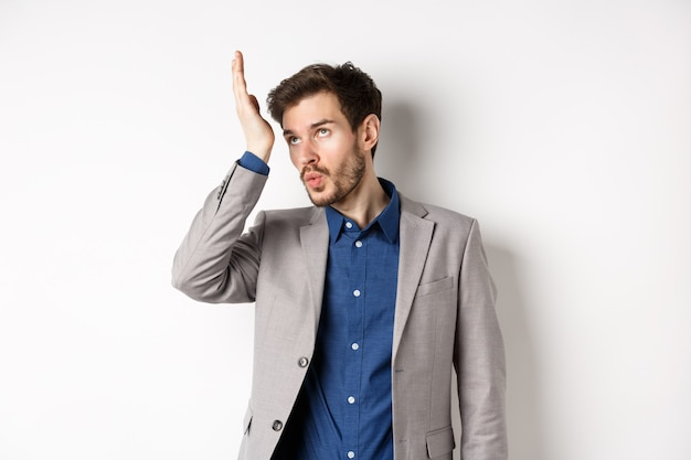 男は非常に愚かな誰かにショックを受けました。イライラしたビジネスマンは、スーツを着て白い背景の上に立って、狂ったクライアントに悩まされている目とfacepalmを転がします。