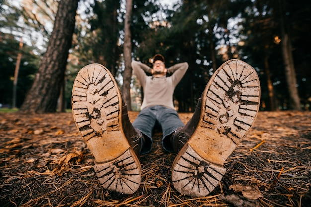A man in  shoes with wooden sole sitting in autumn park