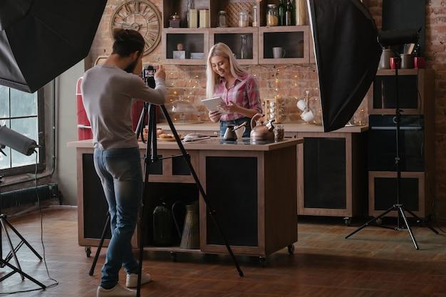 음식 블로거를 촬영하는 사람. 사진 촬영. 타블렛으로 부엌 카운터에 여자입니다. 백 스테이지 사진.