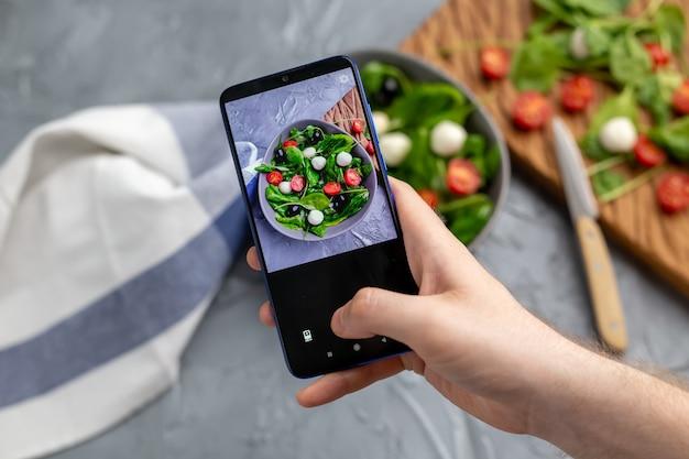 Мужчина снимает салат из свежих овощей с моцареллой и шпинатом на камеру мобильного телефона. готовка