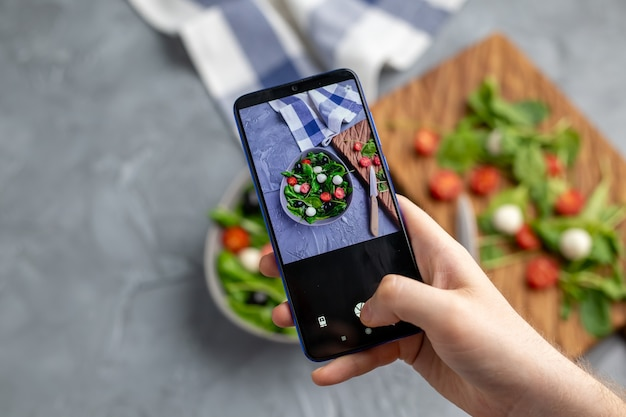 휴대 전화 카메라에 모짜렐라와 시금치와 신선한 야채 샐러드를 촬영하는 남자. 조리