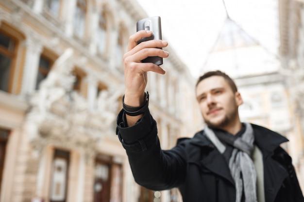 도시 주위를 산책하는 동안 전화에 멋진 건축을 촬영하는 사람.