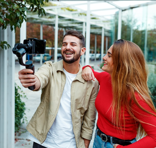 Man shooting a video with gimbal with woman