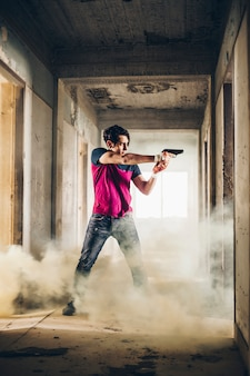 Man shooting with a gun in a ruined building in a steam
