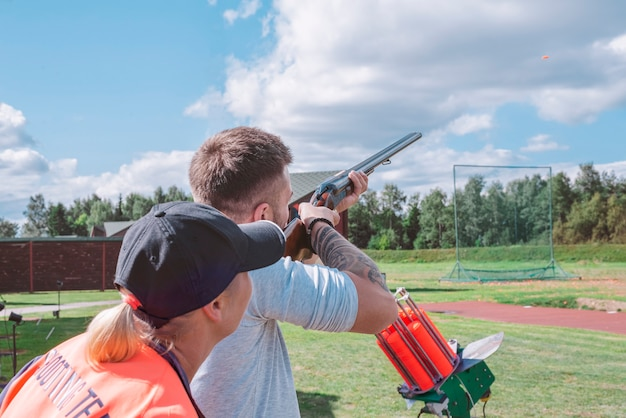 男はインストラクターの監督の下で競技会で狩猟用ライフルで皿を撃ちます。狩猟、射撃の競争の概念。