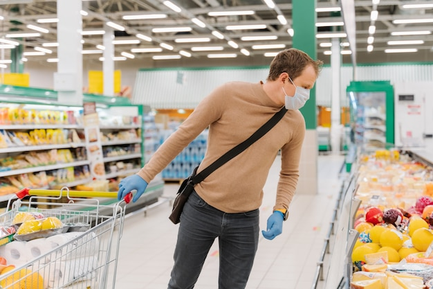 Man shopper wears medical mask, gloves protects from coronavirus, walks with shopping trolley