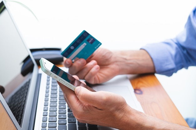 携帯電話とラップトップとクレジットカードで買い物と支払いをする男性。スペースをコピーします。