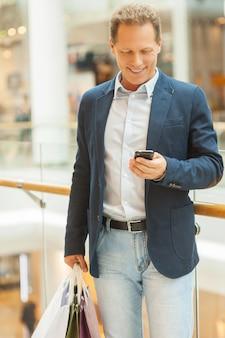 Человек за покупками. веселый зрелый мужчина держит сумки и смотрит на свой мобильный телефон, стоя в торговом центре